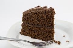 Plasterek czekoladowy tort na bielu talerzu odizolowywającym obrazy stock
