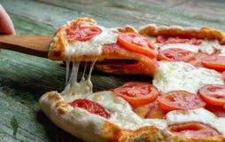 Plasterek pizza na drewniany cedzakowym Fotografia Stock