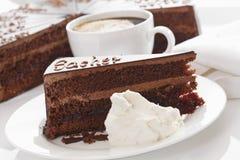 Plasterek Sacher tort w talerzu z kawą zdjęcie stock