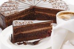 Plasterek Sacher tort w talerzu z kawą fotografia royalty free