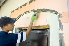 Plasterer. Inflicts plaster on wall Stock Photo