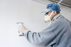 Plasterer. Processes wall by sandpaper before glue on wallpaper Royalty Free Stock Images