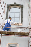 Plasterer. Inflicts mortar on architectural element Stock Images