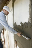 Plasterer. Inflicts mortar on wall Stock Photos