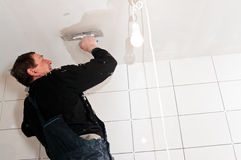 Plasterer at ceiling work. Senior plasterer at ceiling work, making the surface even Stock Photography