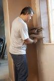 Plasterer che lavora alla parete interna Immagine Stock