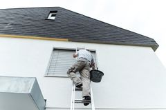 Plasterer climbing up the ladder to cover the roof underside wit Stock Photo
