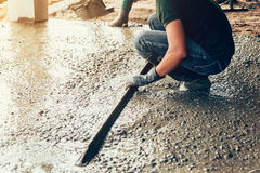 Plasterer concrete worker at floor of house construction.  Stock Photo