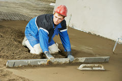 Plasterer concrete worker at floor work. Plasterer at indoor concrete cement floor topping with float Stock Photos