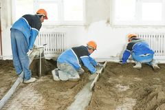 Plasterer concrete worker at floor work Royalty Free Stock Images