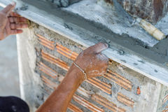 Plasterer concrete worker at wall of house construction Stock Photography