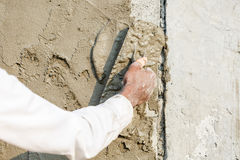 Plasterer concrete worker at wall of house construction Stock Images