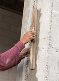 Plasterer concrete worker at wall of house construction Royalty Free Stock Photos
