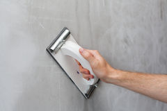 Plasterer erases irregularities on the wall with trowel. Royalty Free Stock Photography