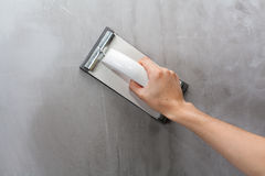 Plasterer erases irregularities on the wall with trowel. Royalty Free Stock Photo