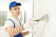 Plasterer with putty knife at wall filling. Plasterer home improvement handyman worker with putty knife working on apartment wall filling Royalty Free Stock Photo