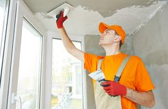 Plasterer at indoor ceiling work. Plasterer at indoor ceiling renovation decoration with float and plaster Stock Photos