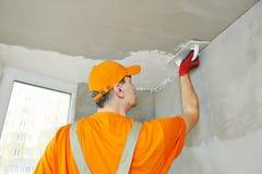 Plasterer at indoor ceiling work. Plasterer at indoor ceiling renovation decoration with float and plaster Stock Image