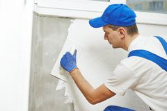 Plasterer at indoor wall work. Plasterer at indoor wall renovation decoration with float and plaster Royalty Free Stock Images