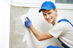 Plasterer at indoor wall work. Plasterer at indoor wall renovation decoration with float and plaster Stock Images