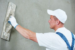 Plasterer at indoor wall work. Plasterer at indoor wall renovation decoration with float and plaster Royalty Free Stock Photography
