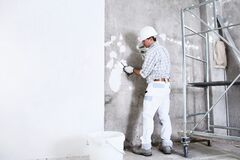 Free Plasterer Man At Work With Trowel Plastering The Wall Of Interior Construction Site Wear Helmet And Protective Gloves, Scaffolding Stock Photos - 175848163