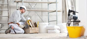 Free Plasterer Man Construction Worker Work With Tool Box Wear Gloves, Hard Hat And Protection Glasses At Interior Building Site With Royalty Free Stock Images - 179284769