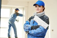 Plasterer Portrait at indoor wall work. Female plasterer painter portrait at indoor wall renovation decoration stopping with spatula and plaster Royalty Free Stock Photography