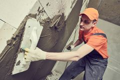 Plasterer putting plaster on wall. slow motion stock photo