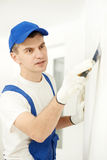 Plasterer with putty knife at wall filling Royalty Free Stock Photography