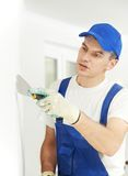 Plasterer with putty knife at wall filling. Plasterer home improvement handyman worker with putty knife working on apartment wall filling Stock Photos