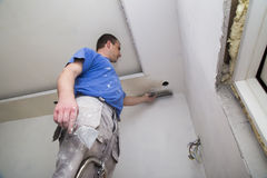 Plasterer with putty knife working on apartment wall Royalty Free Stock Image