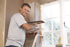Plasterer que trabalha na parede interior