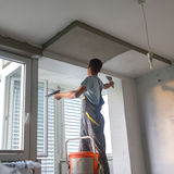 Plasterer renovating indoor walls and ceilings. Construction finishing works. Royalty Free Stock Photos