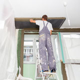 Plasterer renovating indoor walls and ceilings. Finishing works. Royalty Free Stock Photography