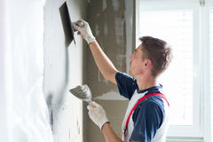 Plasterer renovating indoor walls and ceilings. Stock Photos