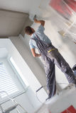 Plasterer renovating indoor walls and ceilings. Royalty Free Stock Photo