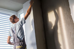 Plasterer renovating indoor walls and ceilings. Royalty Free Stock Photography