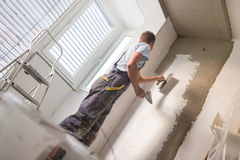 Plasterer renovating indoor walls and ceilings. Thirty years old manual worker with wall plastering tools inside a house. Plasterer renovating indoor walls and Stock Images