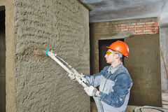 Plasterer spraying plaster on wall. Plasterer operating sprayer equipment machine for spraying thin-layer putty plaster finishing on brick wall Royalty Free Stock Images