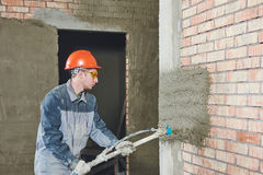 Plasterer spraying plaster on wall Stock Photos