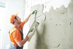 Renovation at home. Plasterer spreading plaster on wall. Plasterer spreading or applying putty plaster layer before finishing coating on brick wall from aerated royalty free stock photo