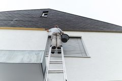 Plasterer staying on ladder and covering the roof underside with Stock Image