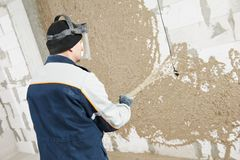 Plasterer at stucco work with liquid plaster Stock Images