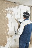 Plasterer at stucco work with liquid plaster. Plasterer at indoor wall renovation decoration spraying liquid plaster from plastering station Royalty Free Stock Photo