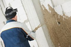 Plasterer at stucco work with liquid plaster. Plasterer at indoor wall renovation decoration spraying liquid plaster from plastering station Royalty Free Stock Images