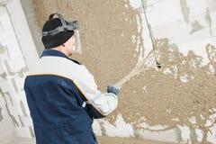 Plasterer sul lavoro dello stucco con intonaco liquido immagini stock