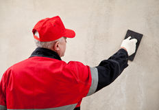 Plasterer in uniform working with float Stock Photo