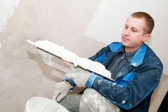 Plasterer at work. Plasterer at indoor renovation decoration with putty knife Royalty Free Stock Photo