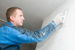 Plasterer at work. Plasterer at indoor renovation decoration with putty knife Royalty Free Stock Photos